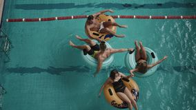 Vista superiore a quattro amici allegri divertendosi mentre nuotando sugli anelli di gomma gonfiabili nello stagno di lusso 4K archivi video