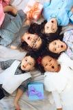 Vista superiore Ritratto dei bambini allegri che si trovano sul pavimento nella forma del cerchio immagini stock libere da diritti