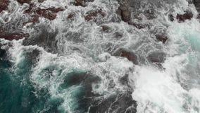 Vista superiore Riva vulcanica ripida, scogliere di lava vulcanica congelata, oceano tempestoso, schiuma bianca dalle onde gigant stock footage