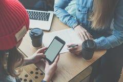 Vista superiore, smartphone del primo piano in mani femminili Una riunione di due amici in caffè Le ragazze imparano online, beve Fotografia Stock Libera da Diritti