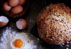 Vista superiore su pane e sulle uova La farina è sparsa vicino, nel centro si trova il tuorlo Cottura della prima colazione fotografia stock