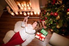 Vista superiore su una ragazza che si trova sotto un albero di Natale immagine stock
