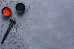 Vista superiore sui bastoncini, sulla soia e sullo zenzero su grey e sul fondo rustici del sesamo Disposizione piana, spazio dell Fotografie Stock