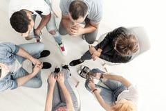 Vista superiore sui giovani che ascoltano lo psicologo nel corso della riunione del gruppo di appoggio fotografia stock libera da diritti