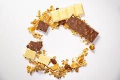 Vista superiore sul cerchio fatto dei muesli del granola/con i frutti secchi Barre di cioccolato tagliate marroni bianche nel cer immagini stock libere da diritti