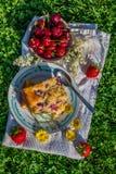 Vista superiore sulla parte di dolce della ciliegia con le fragole mature intorno e le fioriture gialle Immagini Stock Libere da Diritti