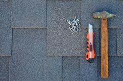 Vista superiore sulle assicelle del bitume dell'asfalto su un tetto con il martello, i chiodi ed il fondo del coltello della canc Fotografia Stock Libera da Diritti