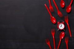 Vista superiore sulle forcelle e sull'orologio di plastica su fondo nero Fotografia Stock