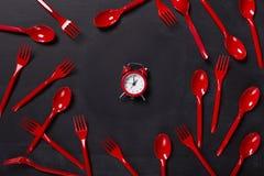 Vista superiore sulle forcelle e sull'orologio di plastica su fondo nero Immagine Stock