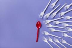 Vista superiore sulle forchette e sul cucchiaio di plastica su fondo viola Fotografia Stock