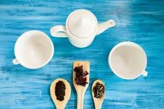 Vista superiore sulle tazze di tè accanto ai cucchiai di legno con le foglie di tè Fotografie Stock