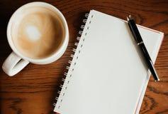 Vista superiore Tazza di caffè con caffè penna che mette sul taccuino in bianco Immagini Stock Libere da Diritti