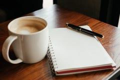 Vista superiore Tazza di caffè con caffè penna che mette sul taccuino in bianco Immagine Stock Libera da Diritti