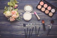 Vista superiore una collezione di trucco cosmetico e di fiore sul fondo di legno della tavola Immagine Stock Libera da Diritti