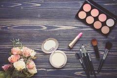 Vista superiore una collezione di trucco cosmetico e di fiore sul fondo di legno della tavola Immagini Stock