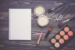 Vista superiore una collezione di trucco cosmetico e di taccuino sul fondo di legno della tavola Fotografia Stock