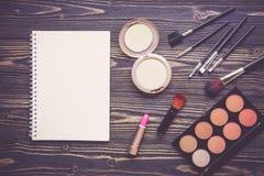Vista superiore una collezione di trucco cosmetico e di taccuino sul fondo di legno della tavola Fotografie Stock Libere da Diritti