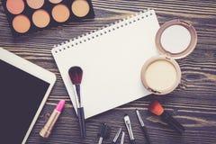 Vista superiore una collezione di trucco cosmetico e di taccuino sul fondo di legno della tavola Fotografia Stock Libera da Diritti