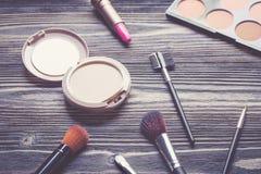 Vista superiore una collezione di trucco cosmetico sul fondo di legno della tavola, concetto cosmetico di modo dei prodotti Immagine Stock
