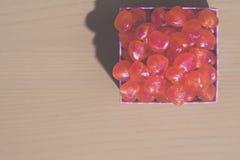 Vista superiore: Una scatola in pieno di cuore ha modellato le caramelle sul backgrou di legno Fotografie Stock