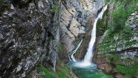 Vista surpreendente da cachoeira Savica em montanhas dos cumes, na água azul profundamente limpa e no parque nacional de Triglav  filme