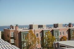 Vista surpreendente de um telhado de um prédio de apartamentos na moda anca que negligencia a água na baía Imagens de Stock