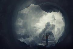 Vista surreale come fuga dell'uomo da una caverna scura che scala le scala mistiche che attraversano l'abisso nebbioso che va su  fotografie stock