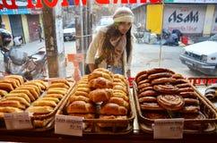 Vista tailandesa dos povos das mulheres do viajante e pão seleto na loja para a compra no thamel foto de stock