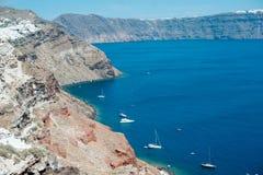 Vista tradizionale dalla riva al mare con le barche bianche sull'isola di Santorini fotografia stock