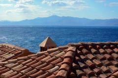 Vista tradizionale di monemvasia della Grecia delle case di pietra con il fondo delle montagne e del mare Immagine Stock