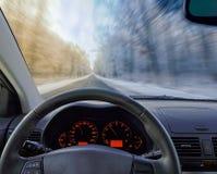Vista tramite il parabrezza dell'automobile alla strada di inverno Fotografie Stock