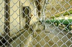 Vista tramite il recinto di filo metallico al vecchio interno della fabbrica Scena della fabbrica I raccolti del trasportatore Gr Immagini Stock