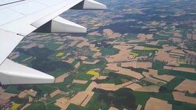 Vista tramite la lampadina degli aerei alla terra, volante su un aeroplano sopra i campi agricoli video d archivio