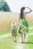 A vista traseira da coberta da jovem mulher eyes do sol e da mão da terra arrendada e das meninas na estrada de terra rural Imagem de Stock