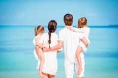 Vista traseira da família de quatro pessoas no branco na praia em férias das caraíbas Os pais com duas crianças apreciam suas Car Fotos de Stock