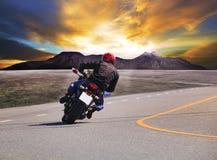 Vista traseira da motocicleta da equitação do homem novo na curva w da estrada asfaltada Imagens de Stock Royalty Free