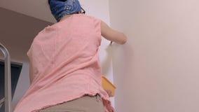 Vista traseira da parede da pintura da mulher com escova de pintura video estoque