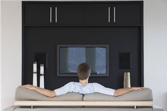 Vista traseira da televisão de observação do homem imagem de stock royalty free
