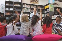 Vista traseira das crianças da escola que levantam a mão na biblioteca para responder em uma pergunta imagem de stock royalty free