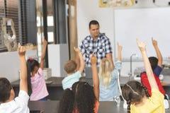Vista traseira das crianças da escola que levantam a mão para responder em uma pergunta do professor no fundo foto de stock royalty free