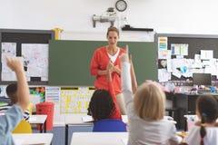 Vista traseira das crianças da escola que levantam a mão para responder em uma pergunta imagens de stock royalty free