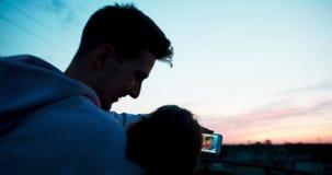 Vista traseira das fotos de observação de sorriso felizes dos pares loving no telefone celular e em apreciar o por do sol no telh vídeos de arquivo