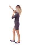 Vista traseira de apontar a mulher bonita nova e de usar um móbil Imagem de Stock Royalty Free