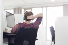 Vista traseira de fones de ouvido vestindo do homem de negócios novo na mesa do computador no escritório foto de stock