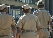 Vista traseira de três sul - oficiais africanos do tráfego, um fêmea e dois homens, tampões vestindo Imagem de Stock Royalty Free