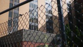 Vista traseira de um hotel ou de um prédio de escritórios como visto da cerca de trás do elo de corrente video estoque