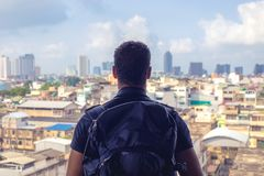 Vista traseira de um mochileiro que olha a cidade do telhado do buildi Fotografia de Stock