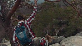 Vista traseira de um trajeto complicado da montanha, e jovens que escalam para baixo o Um turista novo agarra o ramo de um velho filme