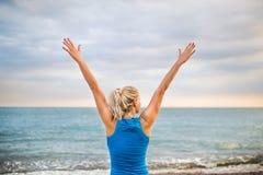 Vista traseira do corredor desportivo novo da mulher no sportswear azul que está na praia foto de stock royalty free