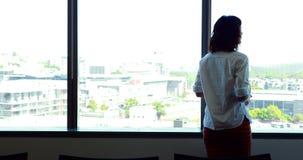Vista traseira do executivo fêmea que olha através da janela filme